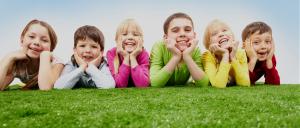 Barn på gressplen som smiler