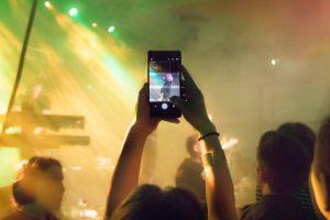 Person som tar bilde med telefon på konsert