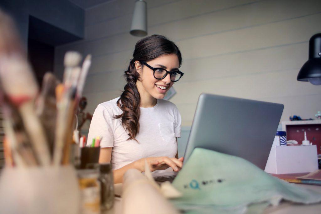 kvinne foran datamaskin som bruker påmeldingssystem